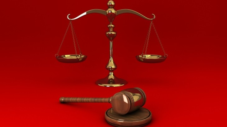 Golden scale and gavel isolated on red solid background